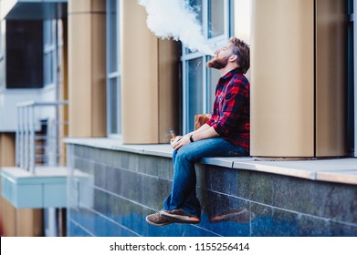 Lifestyle portrait concept. Bearded strolls on the streets of the city among the houses. Smoking and drinking coffee on the background of building close