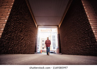 Lifestyle portrait concept. Bearded strolls on the streets of the city among the houses. stroll through the brick arch of the house from afar view