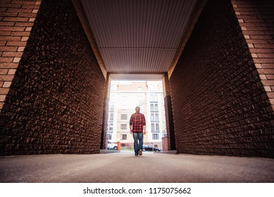 Lifestyle portrait concept. Bearded strolls on the streets of the city among the houses. stroll through the arch of the house from afar view
