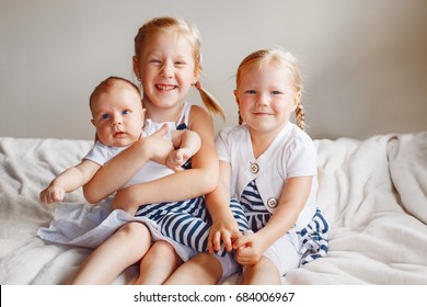 Lifestyle portrait of cute white Caucasian girls sisters holding little baby, sitting on bed indoors. Older siblings with younger brother sister newborn. Family love bonding together concept.
