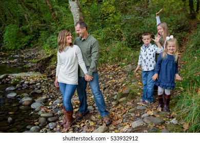 Lifestyle portrait of five people in a family along the banks of the McKenzie River in Oregon.
