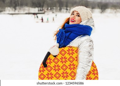 Lifestyle portrait of happy pretty young woman holding saucer sled outdoors at snowing weather. Wearing stylish hat, silver down jacket. Winter sports with snow.  Sledging and winter fun concept