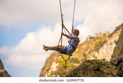 lifestyle portrait of mature attractive and happy woman on with grey hair enjoying amazing rock cliff view from swing feeling young and free swinging carefree having beautiful retirement