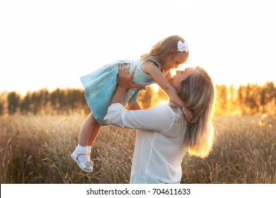 Lifestyle portrait of mom and daughter in happiness at the outside in the meadow wheat field at sunset light. Happy family concept
