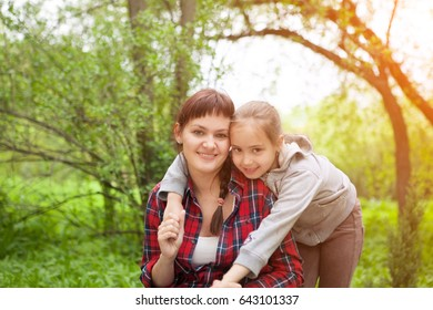 Lifestyle portrait mom and daughter  laughing together outdoors