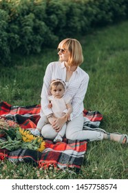Lifestyle portrait of mom and little daughter in happiness at the outside in the meadow field at sunset light. Happy family concept