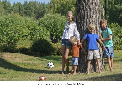 Lifestyle portrait mom and three boys in happiness near the big tree in the park
