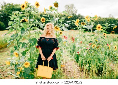 Lifestyle portrait od unusual odd beautiful blonde girl in black embroidery with ornament holding yellow leather bag in flower garden. Country odd woman with emotional funny face wearing enthic dress
