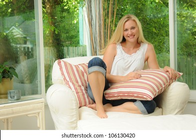 Lifestyle Portrait of a Pretty Blonde Sitting in a Sun Room Setting