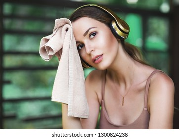 Lifestyle portrait of pretty young sporty woman resting after sports training. Tired and exhausted. Wiping the sweat with a towel. Wearing stylish sportswear top, headphones. Resting after fitness