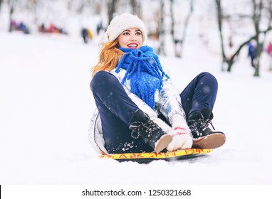 Lifestyle portrait of pretty young woman sliding down hill on snow saucer sled outdoors in winter. Happy face. Emotional photo. Winter sports with snow. Sledding - fun in the mountains. Winter fun