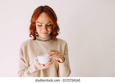 Lifestyle portrait of red haired beautiful girl holding a cup of coffee, looking down dreaming. Wearing cozy sweater of a pastel tone.