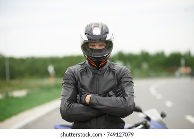 Lifestyle portrait of self determined confident young blue eyed male motorcyclist dressed in stylish leather outfit and helmet, standing outdoors next to his motorbike, keeping arms crossed.