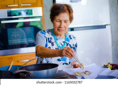 lifestyle portrait of senior happy and sweet Asian Japanese retired, woman cooking at home kitchen alone neat and tidy enjoying preparing meal in elderly and mature home cook concept