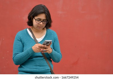 Lifestyle portrait shot of a young Indian woman looking at her mobile phone with focus on her hands while sitting against a red wall background, New Delhi, India