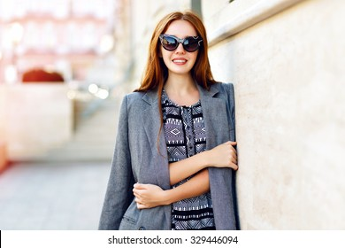 Lifestyle portrait of stunning hipster girl, wearing elegant glamour jacket dress and vintage sunglasses, toned warm colors, positive mood.