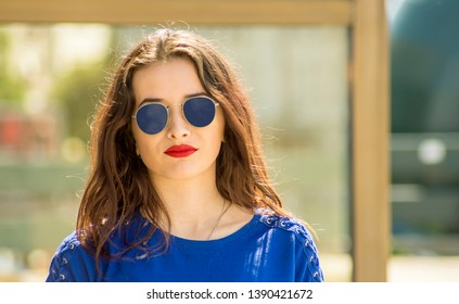 Lifestyle portrait of a stylish woman outdoors reflection in store window in the modern architectural environment