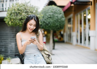 Lifestyle portrait of a stylish young woman looking at phone on the street