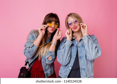 Lifestyle portrait of two  hipster girls best friends with bright make up , making funny faces and sending kiss over pink background.