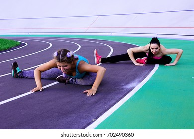 Lifestyle portrait of two young and athletic girls wearing sports wear doing warm-up and workout and stretching at the stadium with cycle track
