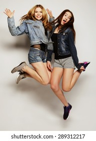 lifestyle portrait of two young hipster girls best friends jump over gray background