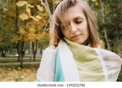 Lifestyle portrait of young adult woman wrapped in scarf with her eyes closed in forest or park, selective focus
