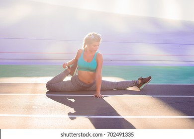 Lifestyle portrait of young and athletic girl wearing sportswear doing warm-up and workout and stretching at the stadium with cycle track