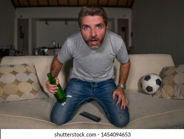 lifestyle portrait of young attractive nervous and excited football supporter man watching soccer game on television at home sofa couch feeling emotion holding beer bottle in disbelief expression