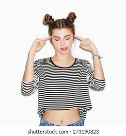 lifestyle portrait of young beautiful girl having fun and showing tongue. Bright makeup and top knot hairdo. White background, not isolated. Inside.
