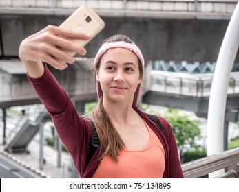 Lifestyle portrait of a Young beautiful girls  tourist standing smile while having fun and taking slefie with smartphone.