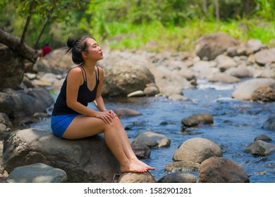 lifestyle portrait of young beautiful and happy Asian Chinese woman carrying sitting relaxed and free on rock trekking on mountains crossing river enjoying nature and fresh envir