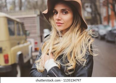 Lifestyle-Portrait von jungen schönen Frauen, die auf den Straßen der Stadt draußen gehen und Hut und Lederjacke tragen. Echte Leute, ehrlich.