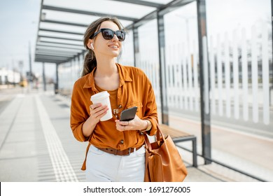 Lifestyle portrait of a young and cheerful woman standing with phone and coffee cup on the public transport stop outdoors. Urban business travel and transportation concept