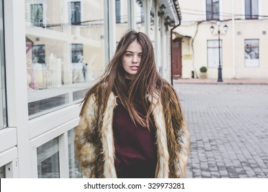 lifestyle portrait of young hipster beautiful caucasian stylish trendy girl with gorgeous long brunette hair is having fun smiling outdoors on the street in the city wooden cool background