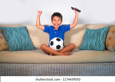 lifestyle portrait of young hispanic boy happy and excited watching football game on television at home living room couch celebrating scoring goal gesturing cheerful as kid soccer crazy fan