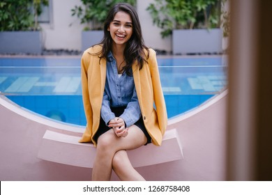 A lifestyle portrait of a young Indian Asian woman in a casual shirt and shorts with a retro yellow jacket draped over her shoulders sitting by a resort pool during the day while on holiday.