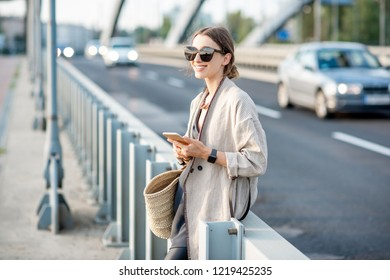 Lifestyle portrait of a young stylish woman with bag and phone outdoors on the modern bridge