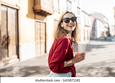 Lifestyle portrait of a young stylish woman dressed in red shirt walking with coffee cup in the old town on a sunny day. Takeaway coffee and woman style concept