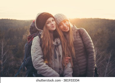 Lifestyle portrait of young traveler best friends girls at sunset, fun and smile