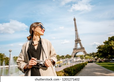 Lifestyle portrait of a young woman tourist standing with photocamera in front of the Eiffel tower in Paris