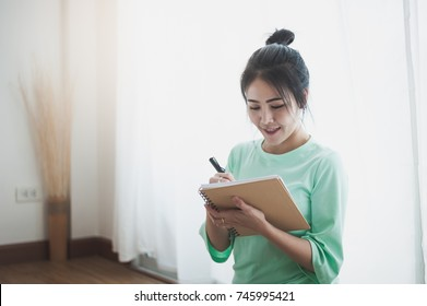 Lifestyle scene of young attractive Asian woman writing journal on notebook beside window in morning time on weekend. Leisure and recreation concept