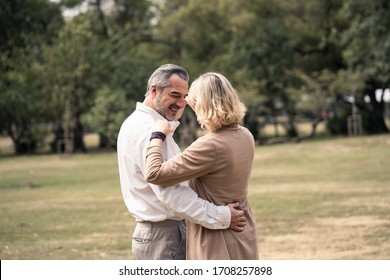 Lifestyle, senior elderly retirement couple dancing together in park. Old man holding woman hip and dance with happiness. Grandparent feels happy with smile face. Enjoy relax time on vacation holiday.