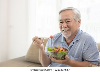 Lifestyle senior man feel happy enjoy eating diet food fresh salad on sofa