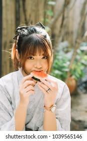 Lifestyle series: Asian woman in yukata eating slice of watermelon