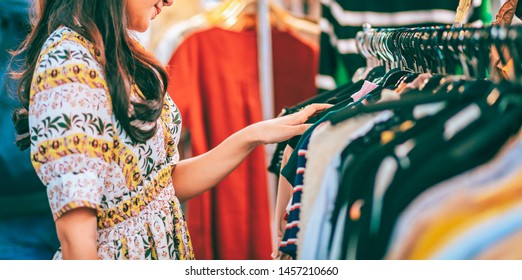 Lifestyle shopping concept, Young happy asian woman with dress choosing cloth in shop store in shopping street at evening, vintage style