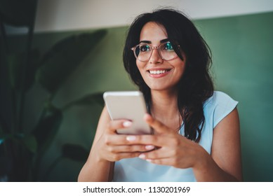 Lifestyle shot of happy businesswoman using modern smartphone device while enjoying coffee break in coffee shop, positive hispanic hipster girl typing text message on touch screen of cellphone