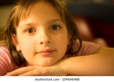 Lifestyle shot of a tween girl looking directly at the camera in natural light with big eyes