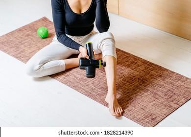 Lifestyle Aufnahme von nicht erkennbaren Frauen, die Selbstmassage-Technik für Beine, die therapeutische perkussive Massage Pistole auf Pilaten Matte zu Hause oder Studioinnenraum.