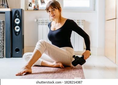 Lifestyle Aufnahme von jungen attraktiven Frauen, die Selbstmassage-Technik für Gesäß, die therapeutische perkussive Massage Pistole auf Pilaten Matte zu Hause oder Studioinnenraum.