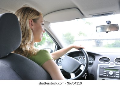 Lifestyle shot of young cheerful woman driving car - rear view